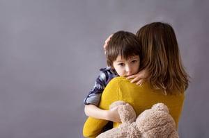 boy hugging mother holding teddy bear