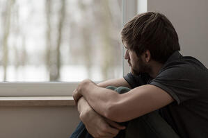 depressed young man staring out window